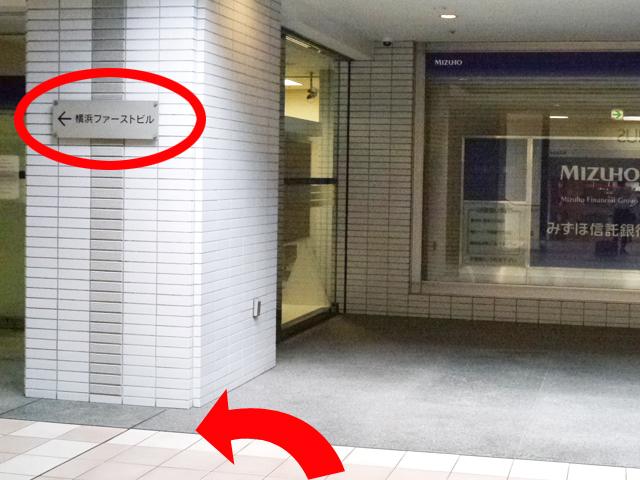 地下街を出たら、左前方にある{red}「横浜ファーストビル」{/red}の標識に従い、{red}左に曲がって直進{/red}してください。