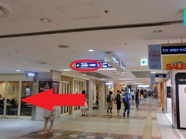 30mほど直進し、{red}「18番出口」{/red}の標識に従い、{red}左に曲がって{/red}ください。 標識の右手に「THE BODY SHOP」があります。