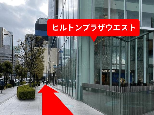 横断歩道を渡り、{red}「ヒルトンプラザウエスト」を右手{/red}に直進してください。