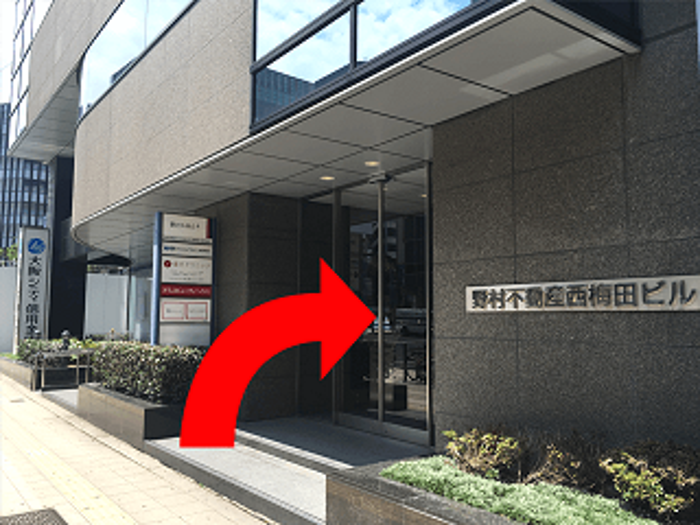 横断歩道を1つ渡った先に{red}1階に「大阪シティ信用金庫」{/red}が入った {red}「野村不動産西梅田ビル」{/red}がございます。 {red}ビルの11階{/red}が会場です。