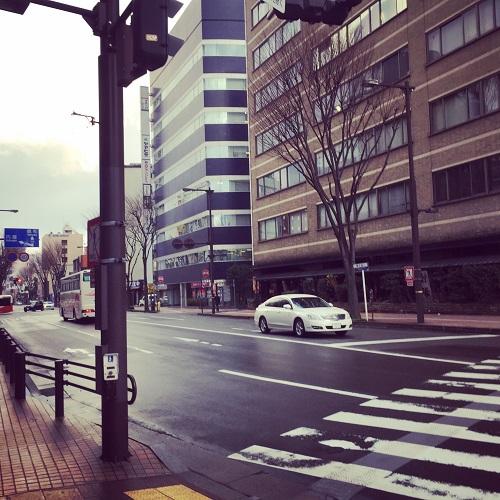 奥の紺色のビルです。信号付きの横断歩道を渡ります。