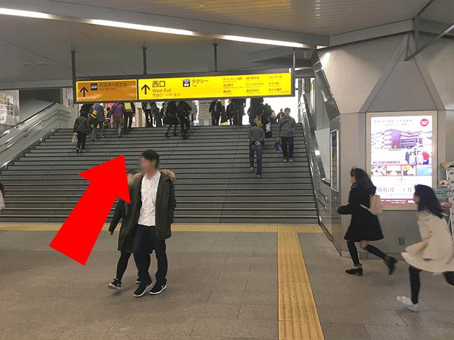 こちらの階段を昇って頂き、西口へ進んでください。