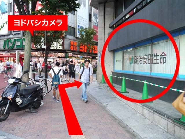 右手にある{red}「明治安田生命新宿ビル」{/red}に沿って進み、左手に{red}「ヨドバシカメラ」{/red}を見る形で{red}右に曲がって{/red}ください。