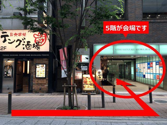 向かい側の「炭火串焼テング酒場」の右手にある{red}「西新宿昭和ビル(NISHI‐SHINJUKU SHOWA  BUILDING)」{/red}の{red}5階{/red}が会場です。