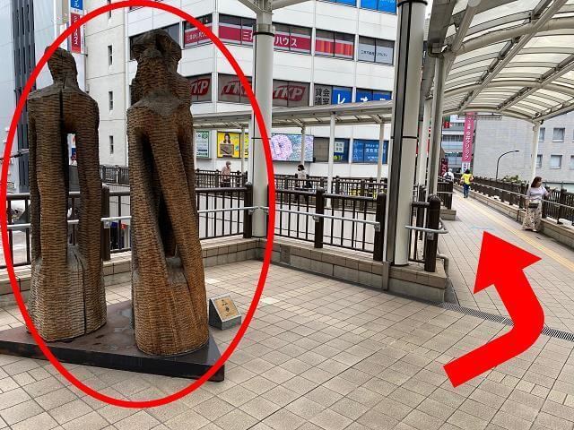 北口{red}ペストリアンデッキの木の彫刻{/red}を{red}右{/red}に曲がります。