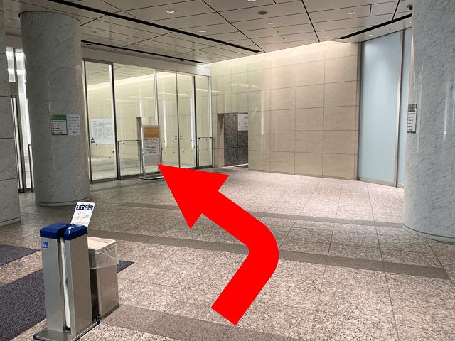 エスカレーターを降りると、マークワンビルエントランスがあります。 エントランスに入り、{red}左手のエレベーターホール{/red}へ進んでください。